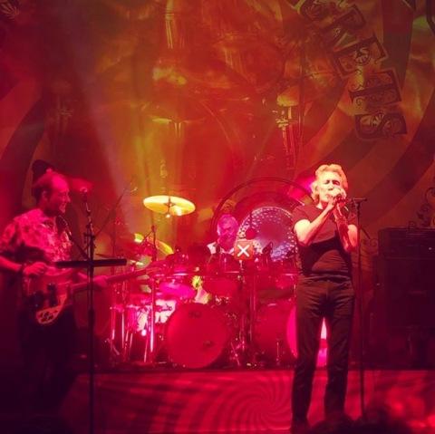 Roger Waters önde söylerken, Nick Mason arkada davul çalıyor.